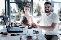 Glimlachende meisje en leraar die terwijl het doorbrengen van tijd in workshop glimlachen royalty-vrije stock fotografie