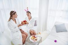Glimlachende meisjes die in badjassen giftdoos houden stock foto