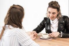 Glimlachende meisjes die bij koffie en het houden van handen zitten terwijl het drinken van koffie Royalty-vrije Stock Afbeeldingen