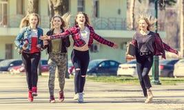 Glimlachende meisjes die onderaan de straat en het hebben van pret lopen Stock Foto's