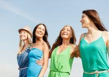 Glimlachende meisjes die op het strand lopen Stock Foto