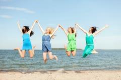 Glimlachende meisjes die op het strand springen Stock Afbeelding
