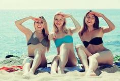 Glimlachende meisjes die op strand zitten stock afbeeldingen