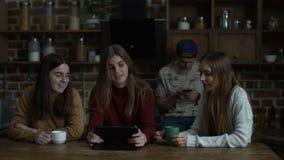 Glimlachende meisjes die over mannelijke vriend in keuken roddelen stock footage