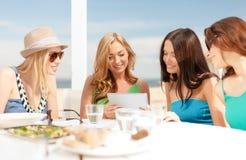 Glimlachende meisjes die tabletpc bekijken in koffie Stock Afbeeldingen