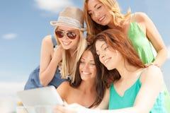 Glimlachende meisjes die tabletpc bekijken in koffie Royalty-vrije Stock Foto's