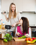 Glimlachende meisjes die thuis koken Stock Foto