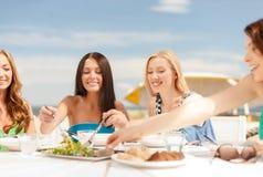 Glimlachende meisjes in koffie op het strand Stock Afbeeldingen