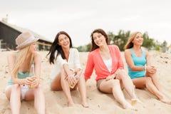 Glimlachende meisjes met dranken op het strand Stock Afbeelding