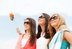 Glimlachende meisjes in schaduwen die pret op het strand hebben Stock Foto