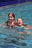 Glimlachende meisjes in zwembad Royalty-vrije Stock Afbeeldingen