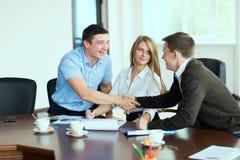 Glimlachende mens bij commerciële vergadering het schudden handen met elkaar Royalty-vrije Stock Afbeeldingen