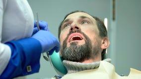 Glimlachende mens bij de tandarts stock video