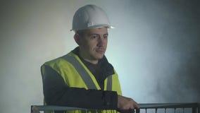 Glimlachende mens in de eenvormige bouwers en helm die zich voor de zwarte achtergrond met schijnwerper bevindt Portret van stock videobeelden