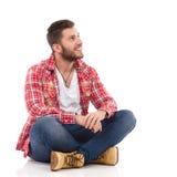 Glimlachende mens in de zitting van het houthakkersoverhemd met gekruiste benen Stock Fotografie