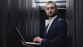 Glimlachende mens die als beheerder in datacentrum met servers werken stock video