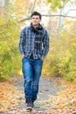Glimlachende mens die in de herfstpark lopen Royalty-vrije Stock Foto's