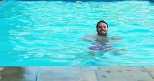 Glimlachende mens die in de pool zwemmen stock videobeelden