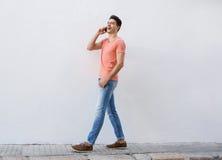 Glimlachende mens die en aan mobiele telefoon lopen luisteren Stock Foto