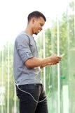 Glimlachende mens die en slimme telefoon zich buiten bevinden met behulp van Stock Afbeelding
