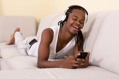 Glimlachende mens die en telefoon met behulp van liggen Stock Foto