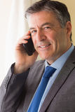 Glimlachende mens die iemand met zijn mobiele telefoon roept Stock Foto