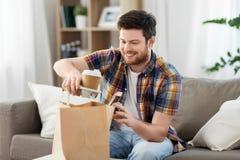 Glimlachende mens die meeneemvoedsel thuis uitpakken royalty-vrije stock foto
