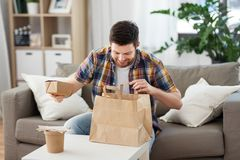 Glimlachende mens die meeneemvoedsel thuis uitpakken stock afbeeldingen