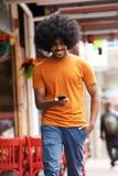 Glimlachende mens die met cellphone in stad lopen Stock Foto's