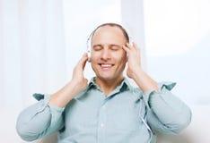 Glimlachende mens die met hoofdtelefoons aan muziek luisteren Royalty-vrije Stock Foto's