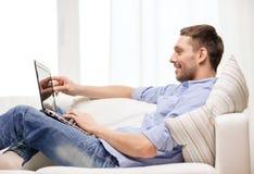 Glimlachende mens die met laptop thuis werken Royalty-vrije Stock Afbeeldingen