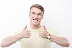 Glimlachende mens die omhoog op geïsoleerde achtergrond beduimelen Royalty-vrije Stock Foto's
