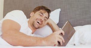 Glimlachende mens die op bed liggen die zijn digitale tablet 4K 4k gebruiken stock video