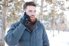 Glimlachende mens die op de telefoon in de winterpark spreken Stock Afbeeldingen
