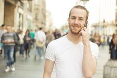 Glimlachende Mens die op mobiele telefoon, stadsstraat spreekt Royalty-vrije Stock Foto