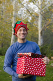 Glimlachende mens die twee Kerstmisgiften houden Stock Foto's