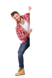 Glimlachende mens die uit van achter witte banner springen Royalty-vrije Stock Afbeelding