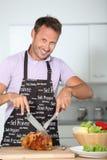 Glimlachende mens die voedsel voorbereidt Stock Foto's