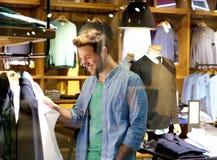 Glimlachende mens die voor kleren bij kledingsopslag winkelen Royalty-vrije Stock Foto's