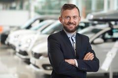 Glimlachende mens die zich in het moderne auto centrum en stellen bevinden royalty-vrije stock fotografie