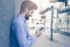 Glimlachende mens die zich op straat en het gebruiken van mobiele telefoon bevinden stock fotografie