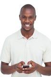 Glimlachende mens die zijn mobiele telefoon met behulp van Royalty-vrije Stock Foto's