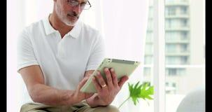 Glimlachende mens die zijn tablet gebruiken stock video
