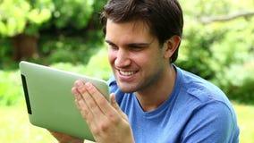 Glimlachende mens die zijn tabletcomputer met behulp van stock videobeelden