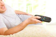 Glimlachende mens het letten op televisie stock afbeeldingen