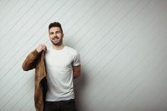 Glimlachende mens in leeg t-shirt en jasje, witte houten muurachtergrond stock foto's