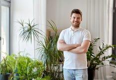 Glimlachende mens met houseplants thuis royalty-vrije stock foto's