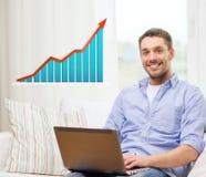 Glimlachende mens met laptop en de groeigrafiek thuis Royalty-vrije Stock Foto's