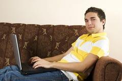Glimlachende mens met laptop huis Stock Foto's