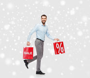 Glimlachende mens met rode het winkelen zakken over sneeuw Stock Foto's